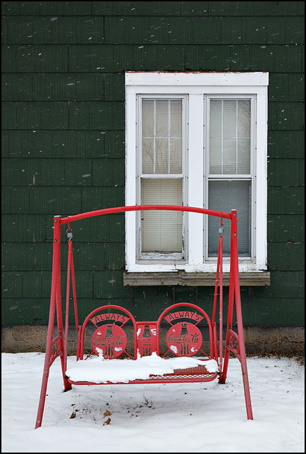 Coca-Cola porch swing in front of an old house in a