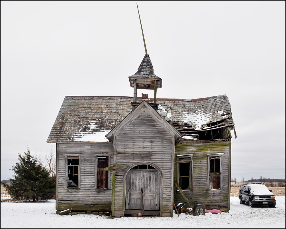 An abandoned one-room wood-frame schoolhouse on Convoy Road in rural Van Wert County, Ohio. The windows are all broken out but the belfry still stands atop the sagging slate roof.
