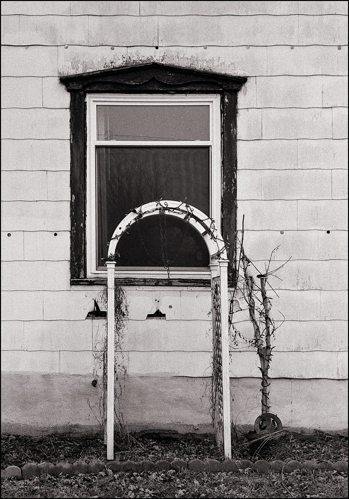A garden arch with Christmas lights on it stands in front of an old house on Randolph Street in the small town of Garrett, Indiana.