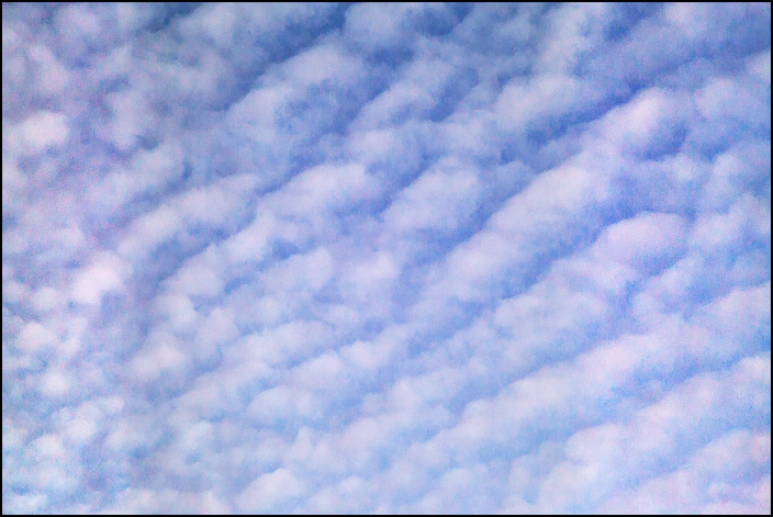 Abstract photograph of a November evening sky with diagonal lines of clouds.