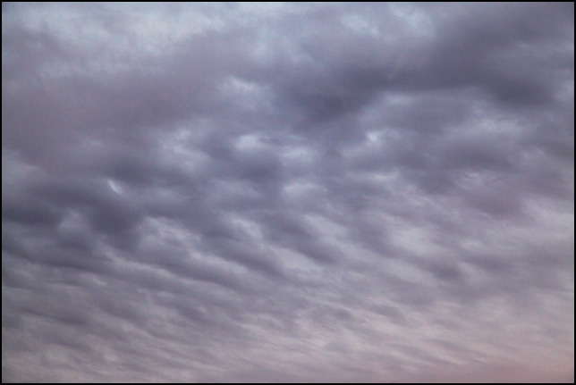 Abstract photograph of a striped pattern of dark clouds in a gray and red sky on a November evening in rural Allen County, Indiana.