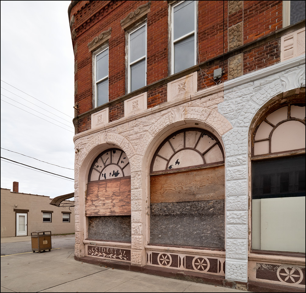 The C. J. Schneider Building on Main Street in the small town of Antwerp, Ohio. The brick and stone building has arched windows  on the first floor that are boarded up, and it says Occidental under one of them.