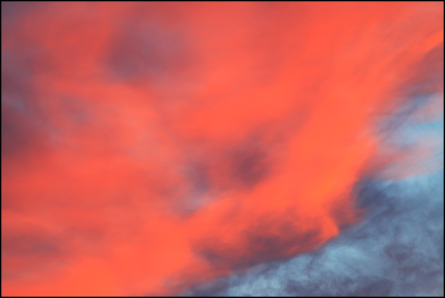Abstract photograph of dramatic orange clouds in a blue sky at sunrise on a December morning in Fort Wayne, Indiana.