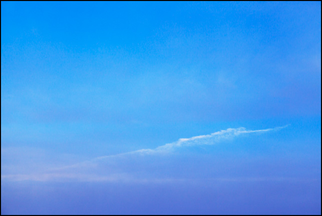 Abstract photograph of a blue sky with bands of purple clouds an hour after sunrise. A thin white cloud runs diagonally across the middle of the sky.