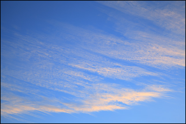 Abstract photograph of bands of thin yellow clouds running diagonally across the middle of the blue sky near sunset. Photographed in the Waynedale area of Fort Wayne, Indiana.
