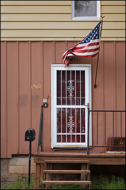 An American flag draped over the porch light above the wrought iron screen door of an old house on High Street in Fort Wayne, Indiana.