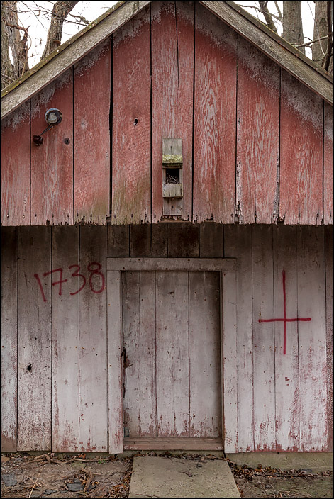 An old weatherbeaten shed at an abandoned farm on Lower Huntington Road in rural Allen County, Indiana. The number 1738 and an upside-down cross are spray painted on the front of it, and a small birdhouse is mounted above the door.
