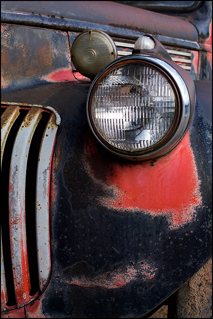 The drivers side headlamp and grille on a black 1941 Chevrolet pickup truck.
