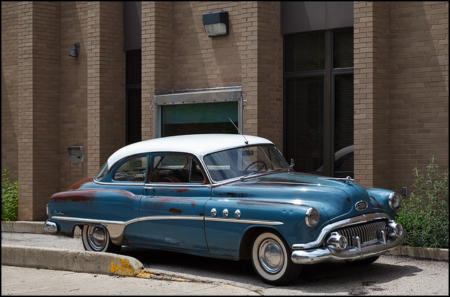 A blue 1951 Buick 8 Coupe with Dynaflow transmission sits next to an abandoned bank in downtown Muncie, Indiana.
