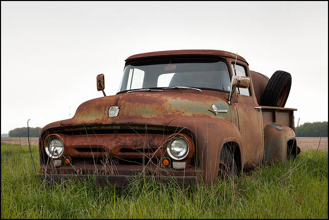 A rusty 1956 Ford F-250 pickup truck sits abandoned in tall grass on the edge of a field in rural Adams County, Indiana.