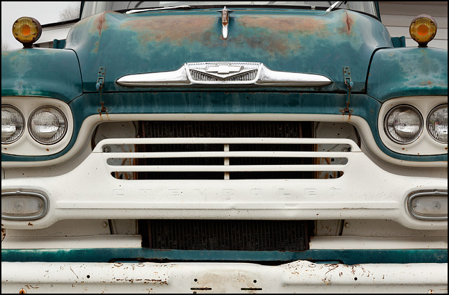 The front of a turquoise 1958 Chevrolet Viking LCF truck showing a closeup view of the grill and headlights.