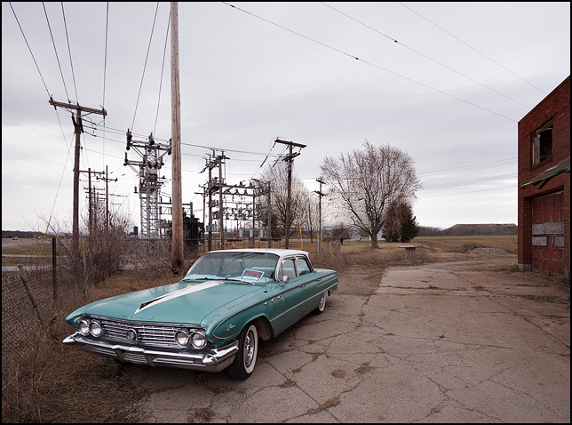 A turquoise 1961 Buick LeSabre sedan in front of an electrical substation and an abandoned brick industrial building on US-27 in rural Allen County, Indiana.