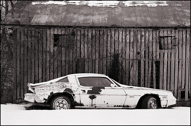 A white 1980 Chevrolet Camaro sits in the snow in front of an old weatherbeaten barn on US-33 in rural Noble County, Indiana.