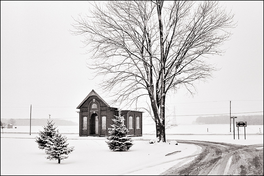 Snow covers the crossroads of Besancon, Indiana. The road splits to go around the abandoned Jefferson Township Center Schoolhouse on Lincoln Highway.