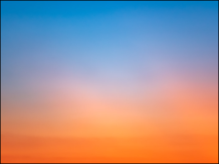 An abstract photograph of the sky at sunset transitioning from blue at the top to deep orange at the bottom with two white lines of clouds. This is in northwest rural Allen County, Indiana.