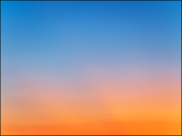 An abstract photograph of the sky at sunset transitioning from deep blue at the top to deep orange at the bottom. This is in northwest rural Allen County, Indiana.