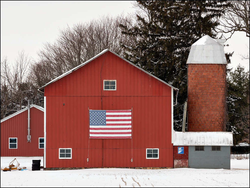 A large American Flag on the side of a red barn along I-469 in rural in Allen County, Indiana. Photographed in winter with snow covering the field in front of the barn.