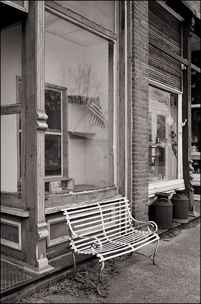 An American flag in the window of a vacant storefront on Main Street in the small town of Hudson, Indiana. A wrought iron park bench stands on the sidewalk under the window.