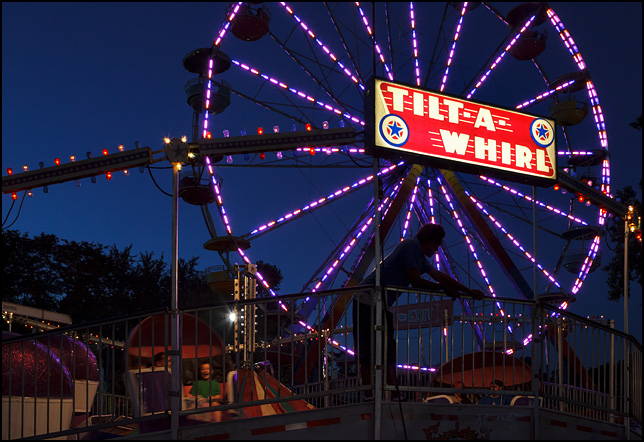 The ride attendant silhouetted against the bright lights of the Tilt-A-Whirl ride and the Ferris Wheel at dusk during the Three Rivers Festival carnival in Fort Wayne, Indiana.