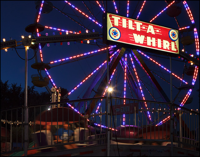 The Tilt-A-Whirl ride is a blur of movement and colorful lights in front of the Ferris Wheel at the Three Rivers Festival carnival in Fort Wayne, Indiana.