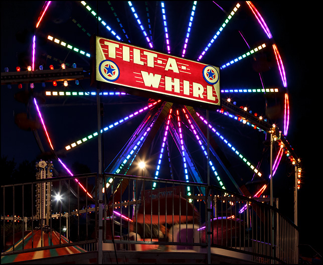 The Tilt-A-Whirl ride in motion in front of the Ferris Wheel at night at the Three Rivers Festival carnival in Fort Wayne, Indiana.