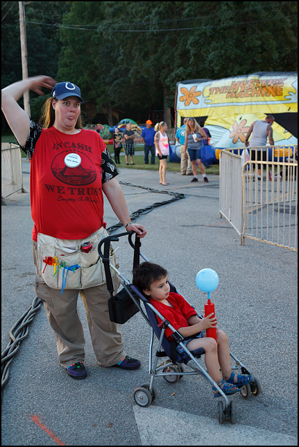 A young boy in a stroller blowing up a balloon with a hand-pump at the 2016 Churubusco Turtle Days carnival in the small town of Churubusco, Indiana. His mother, who is pushing the stroller, worked at the carnival making balloon animals.