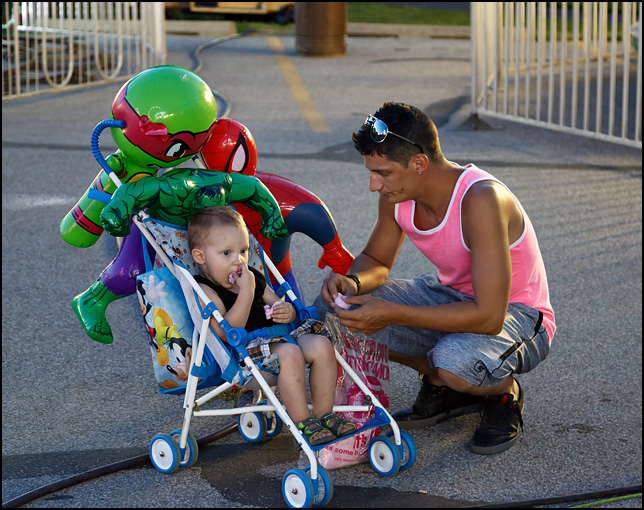 A young man and his son eating cotton candy at the 2016 Churubusco Turtle Days carnival in the small town of Churubusco, Indiana. The little boy sits in a stroller with several inflatable super heroes that they won at the carnival games.