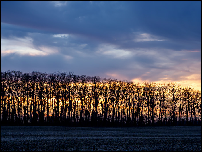 The sun sets behind a line of trees on the edge of a field under a dramatic sky with dark clouds on US-33 in rural northwest Allen County, Indiana.