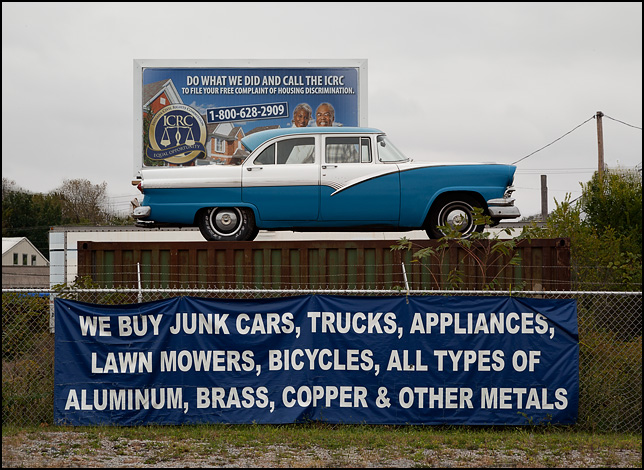 A blue 1956 Ford Fairlane sedan on top of a shipping container at 3 Rivers Metal Recycling on Brooklyn Avenue in Fort Wayne, Indiana. The banner under the classic car says, We buy junk cars trucks appliances lawn mowers bicycles and all types of aluminum brass copper and other metals.