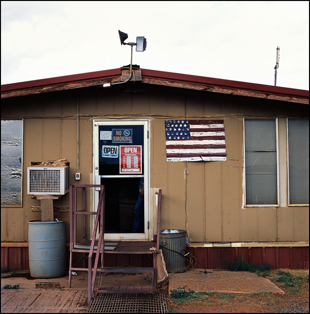 A hand-painted American flag on a sheet of metal hanging next to the door of the 4D Truck Washout and Livestock Rest near Sayre, Oklahoma.