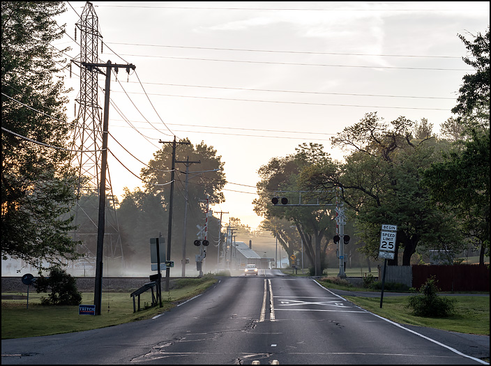 A car approaching the railroad crossing on Sandpoint Road in Fort Wayne, Indiana, at sunrise on a foggy spring morning.