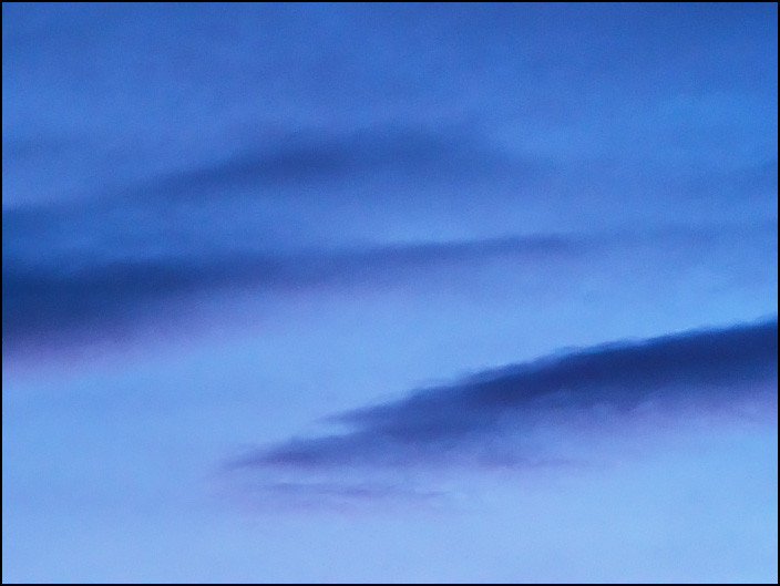 An abstract photograph of waves of dark purple clouds in the sky at last light on a May evening in Fort Wayne, Indiana.