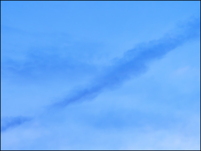 An abstract photograph of a blue sky with a long dark cloud at dusk on a May evening in Fort Wayne, Indiana.