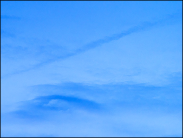 An abstract photograph of a long dark cloud arching across larger clouds in the sky at dusk on a May evening in Fort Wayne, Indiana.