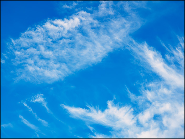 Abstract photograph of shapes formed by white clouds in a blue sky over Fort Wayne, Indiana.