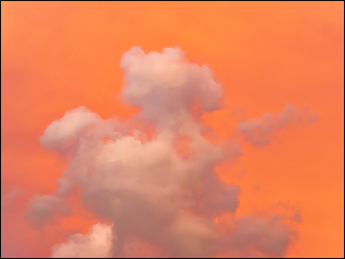 An abstract photograph of a fluffy cloud in an orange sky at sunset in Fort Wayne, Indiana.