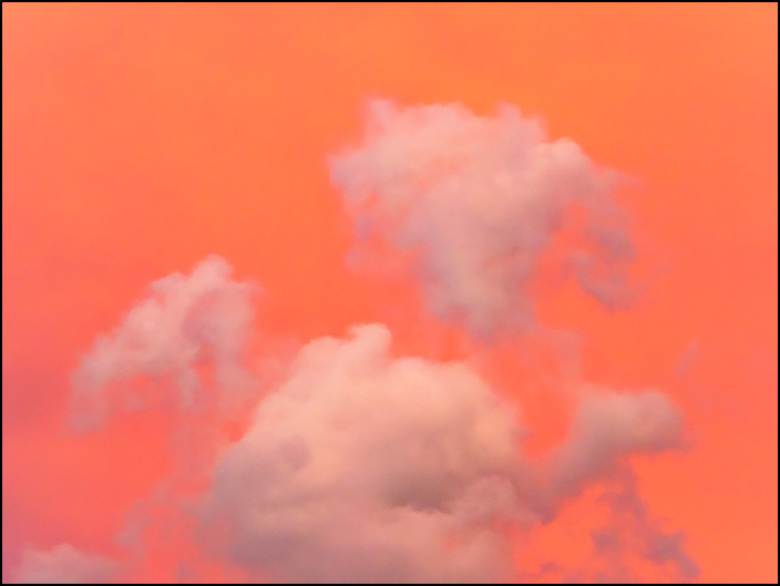 An abstract photograph of a fluffy cloud in a red-orange sky at sunset in Fort Wayne, Indiana.