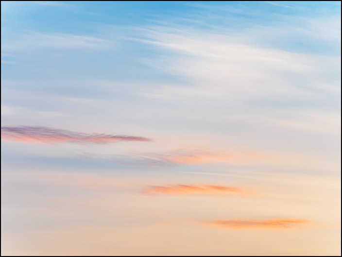 Abstract image of the sky at sunrise in Fort Wayne, Indiana. White and orange clouds in a warm colored sky.