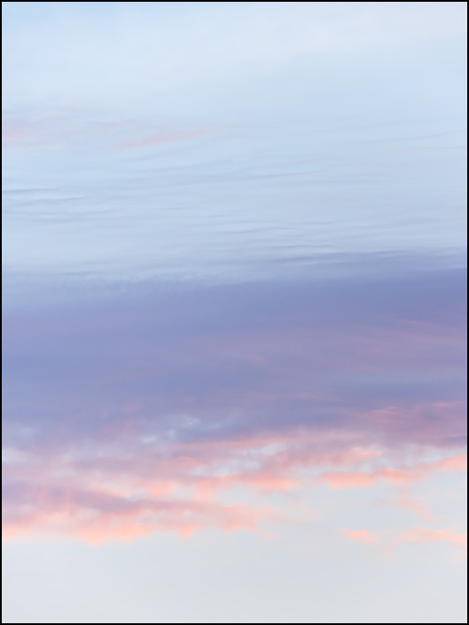 Abstract image of the sky at sunrise in Fort Wayne, Indiana. A purple cloud stretches across a pale blue sky.