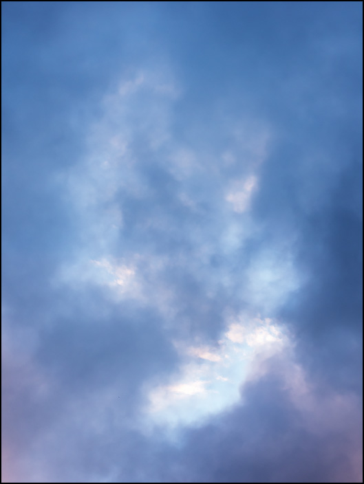 An abstract photograph of dark July storm clouds breaking up in the early morning over Fort Wayne, Indiana.