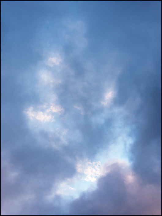 An abstract photograph of dark July storm clouds breaking up to reveal a blue sky in the early morning over Fort Wayne, Indiana.