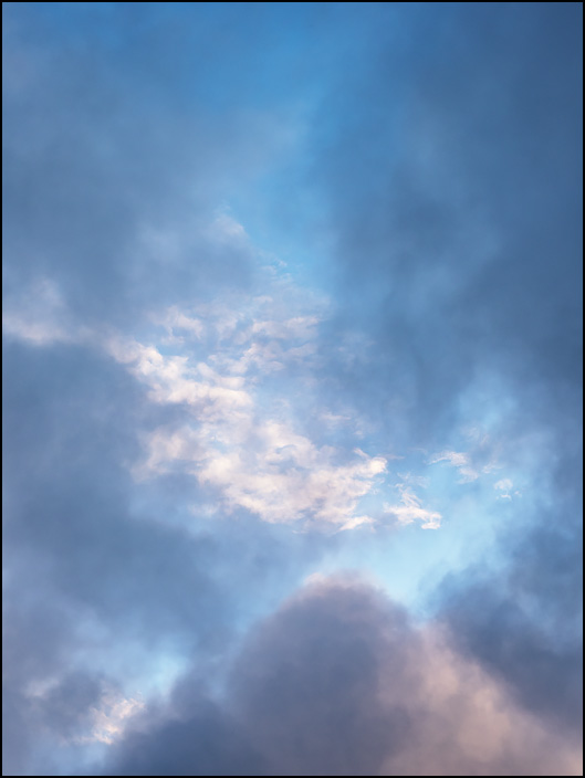 An abstract photograph of a blue sky surrounded by dark clouds in the early morning over Fort Wayne, Indiana.