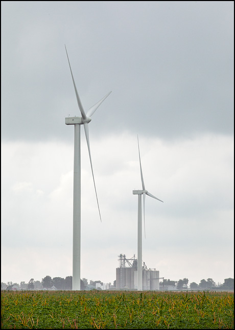 Two wind turbines in a soybean field on a rainy day in Paulding County, Ohio. The grain elevator in the small town of Edgerton, Indiana is visible in the background.
