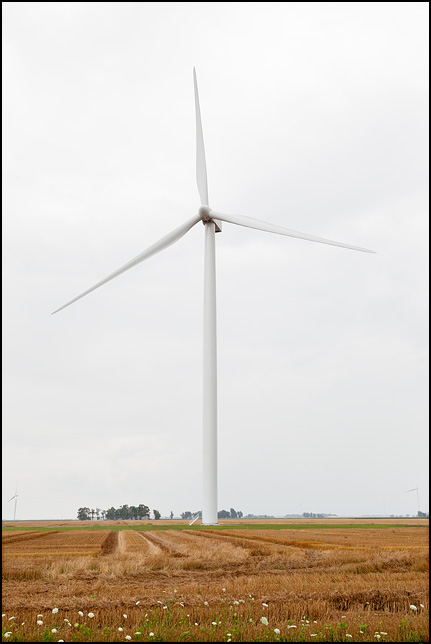 A wind turbine in a partially harvested hayfield in Paulding County, Ohio. It is on the Ohio side of State Line Road.