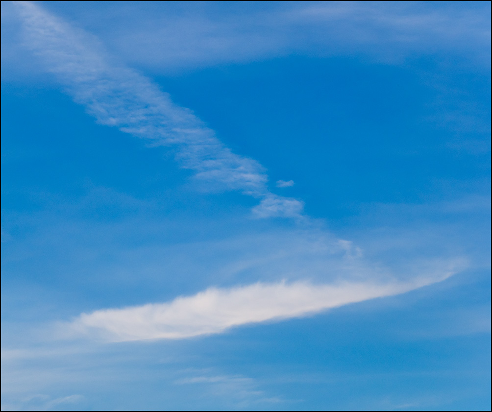 An abstract photograph of linear white clouds forming a square pattern in a blue sky in the evening in Churubusco, Indiana.