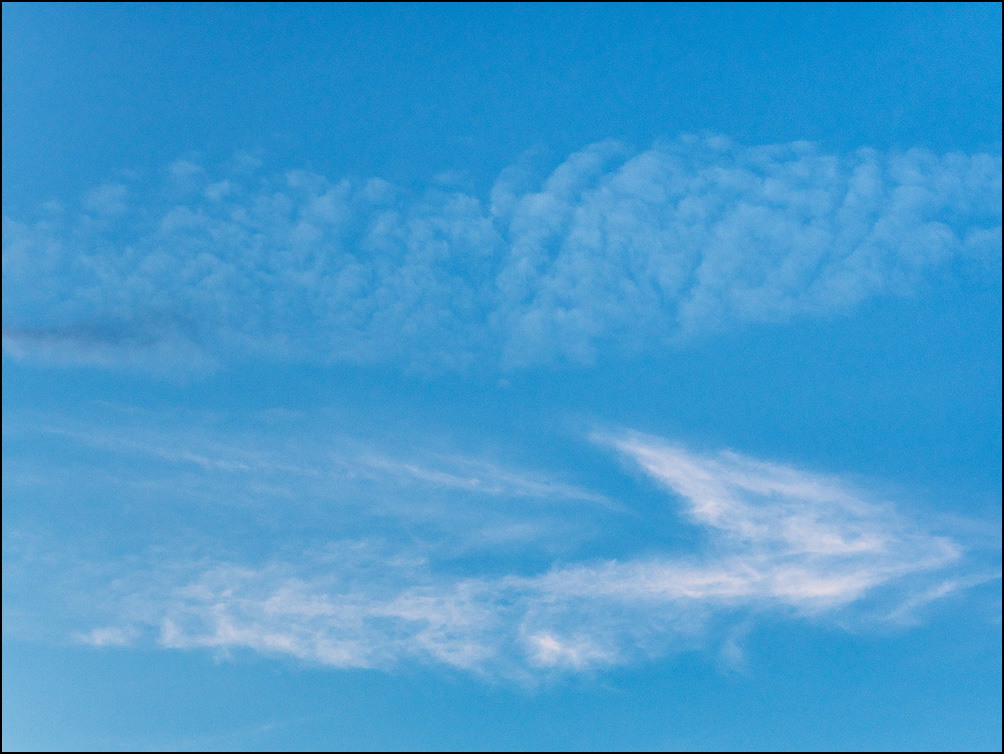 An abstract photograph of a white cloud formation in the shape of a boomerang under a field of white spots in a blue sky. Photographed in the early evening at the end of August in Fort Wayne, Indiana.