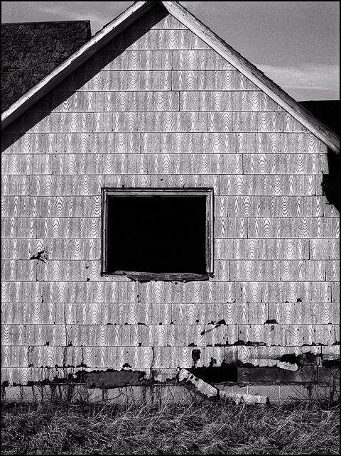 A broken out window in the side of an old abandoned farmhouse with asphalt shingle siding along interstate 69 in Huntington County, Indiana near Warren.