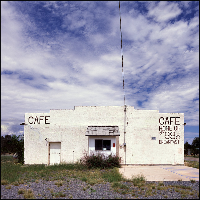 An abandoned restaurant in the small town of Encino, New Mexico. The sign on the adobe building says it is the Home of the 99 cent breakfast.