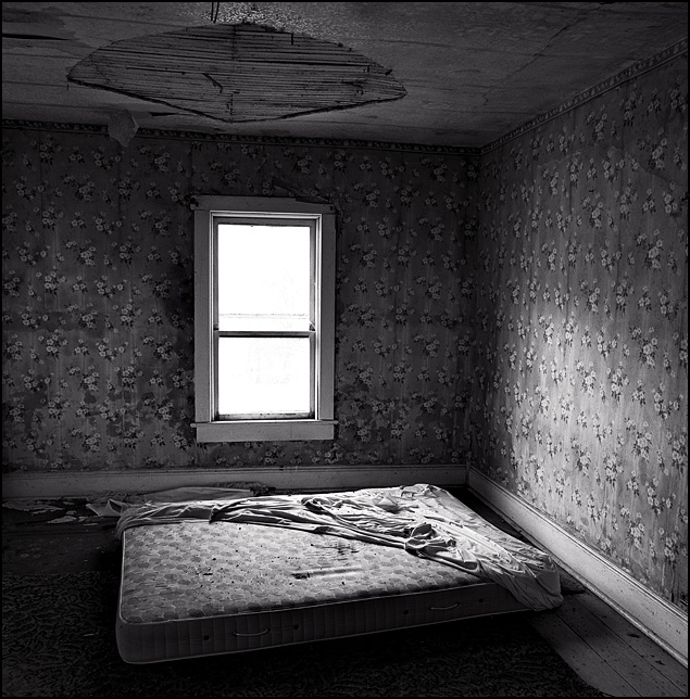 A dirty old mattress on the floor of the bedroom in an abandoned farmhouse.