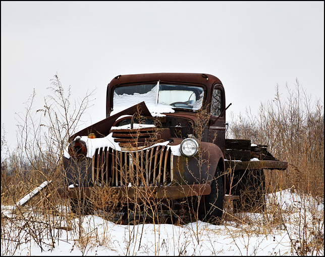 An abandoned Chevrolet truck from the 1940s rusting away in the middle of a snow-covered field at a farm on Knoll Road in Fort Wayne, Indiana.